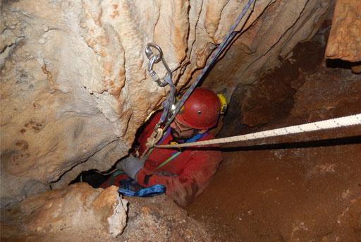 Speleologo visto dall'alto che scende in una grotta illuminata da un fanale